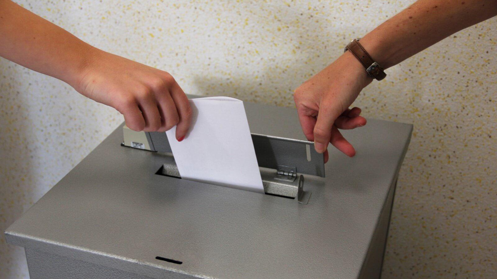 Bild von einem Wahlschein der in die Wahlurne geworfen wird