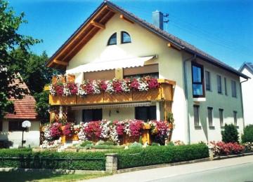 Bild eines Hauses in Winzeln Richtung Flugplatz im Sommer mit Blumenschmuck