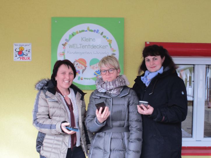 Kindergartenleiterin und Eltern mit Handys